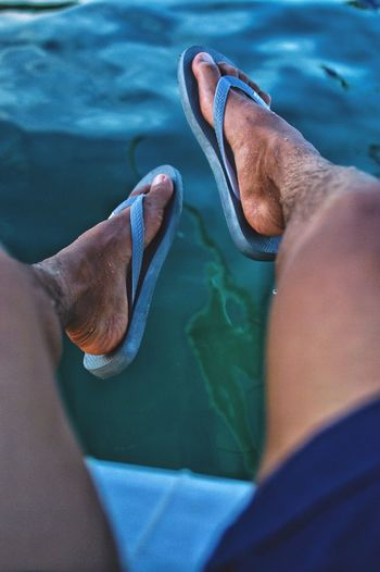 Low section of man legs above swimming pool