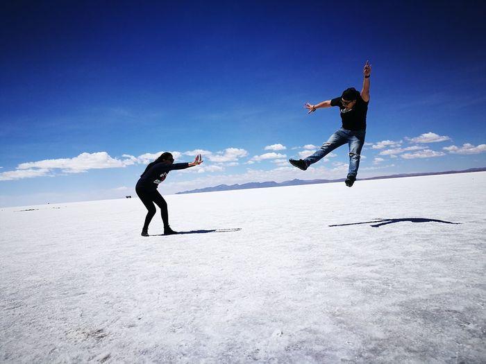 Optical illusion of woman throwing man on salt flat at salar de uyuni