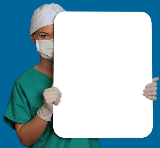 Young woman doctor keeping a white board, against a blue background. Copy Space Doctor  Healthcare Medicine Nurse White Board Blue Blue Background Front View Healthcare And Medicine Keeping Looking At Camera Medical Cannabis Message One Person People Physician Placard Portrait Real People Studio Shot Surgical Mask White Background Young Adult Young Women