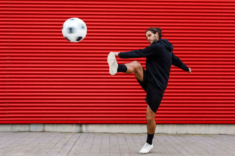 Full length of man with ball against red wall