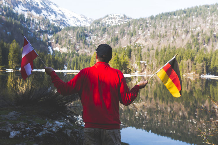 Rear view of mature man holding national flags while standing by lake against mountain