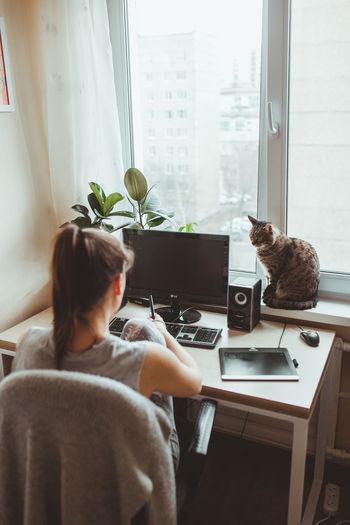 Rear view of woman using desktop pc
