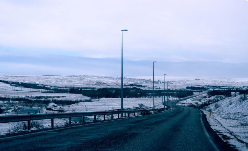 Road passing through snow covered landscape