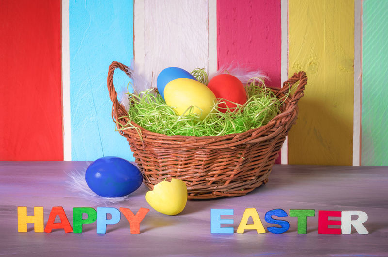 Decorative wicker basket with painted eggs and the words happy easter written with multicolor wooden letters and a colorful fence in the background. Celebration Christian Christianity Easter Easter Egg Holidays Basket Colored Eggs Colorful Food Food And Drink Multi Colored Painted Eggs Religion Wicker Basket