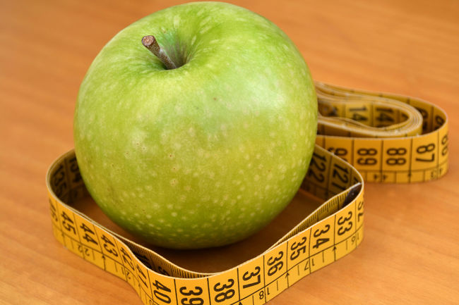 Apple to symbolize a healthy diet to keep fit Apple Apple - Fruit Calories Centimeter Close-up Concept Diet Focus On Foreground Food Fresh Freshness Fruit Green Green Color Healthy Healthy Food Healthy Lifestyle Lifestyle Meter Nutrition Organic Vegan Food Vitamins Weight Loss Weightloss