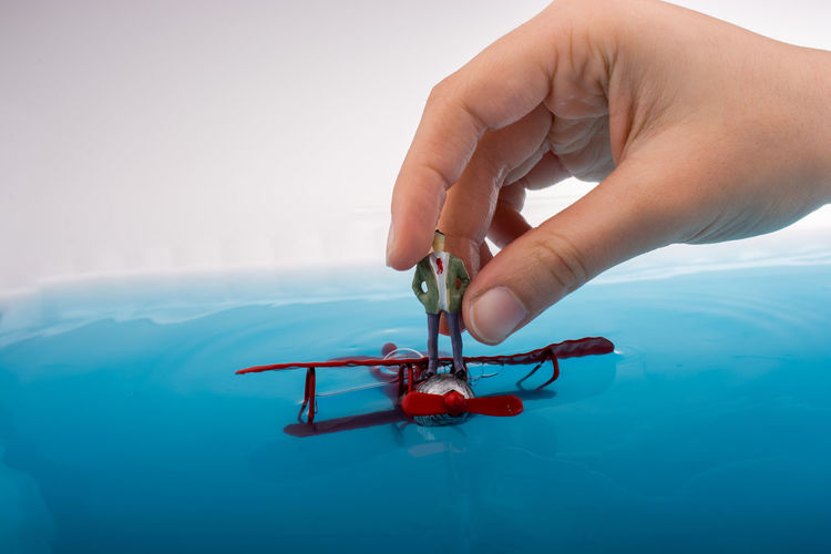 Cropped hand of person holding figurine on model airplane in blue water