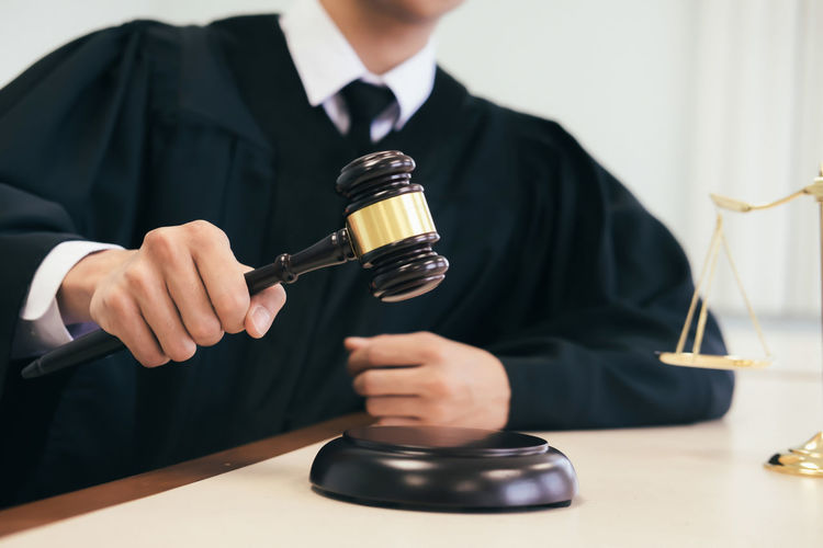 Midsection of judge banging gavel on table