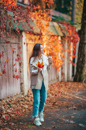 Woman holding umbrella standing by autumn leaves