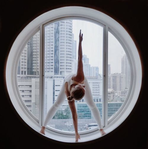 Full Length Of Woman Exercising At Circular Window
