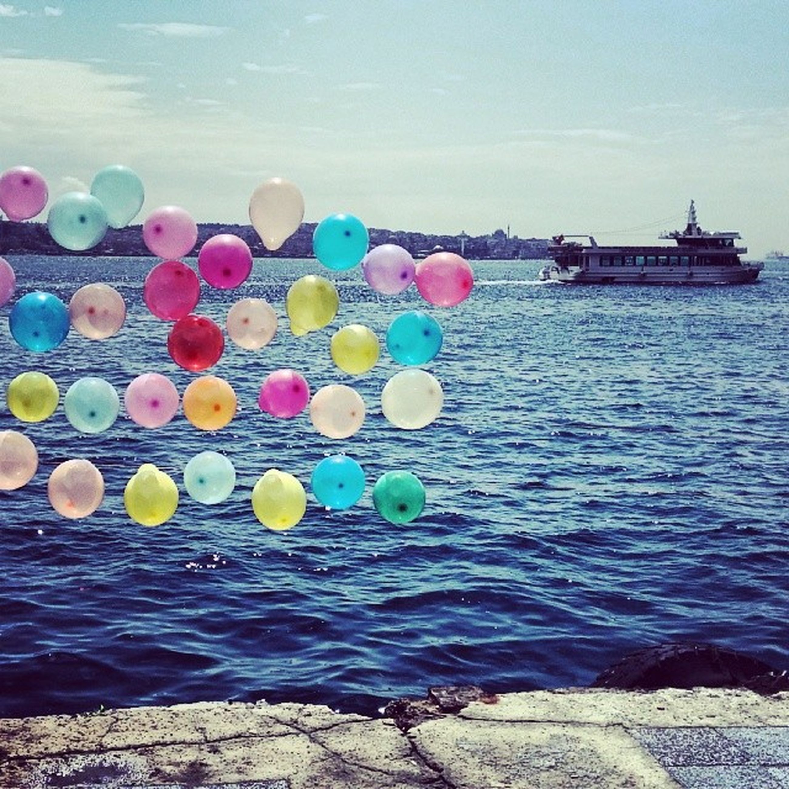 water, sea, multi colored, sky, balloon, blue, horizon over water, nature, tranquility, colorful, beauty in nature, tranquil scene, outdoors, scenics, day, variation, no people, abundance, reflection, large group of objects