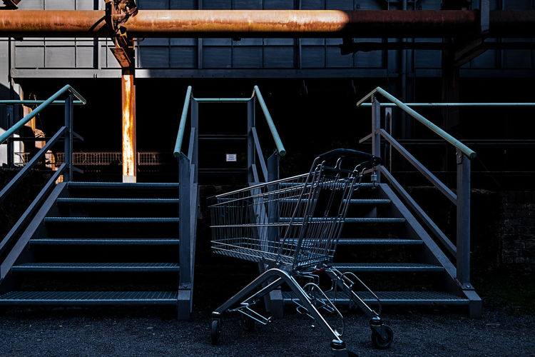 Shopping cart in front of staircase in industrial plant