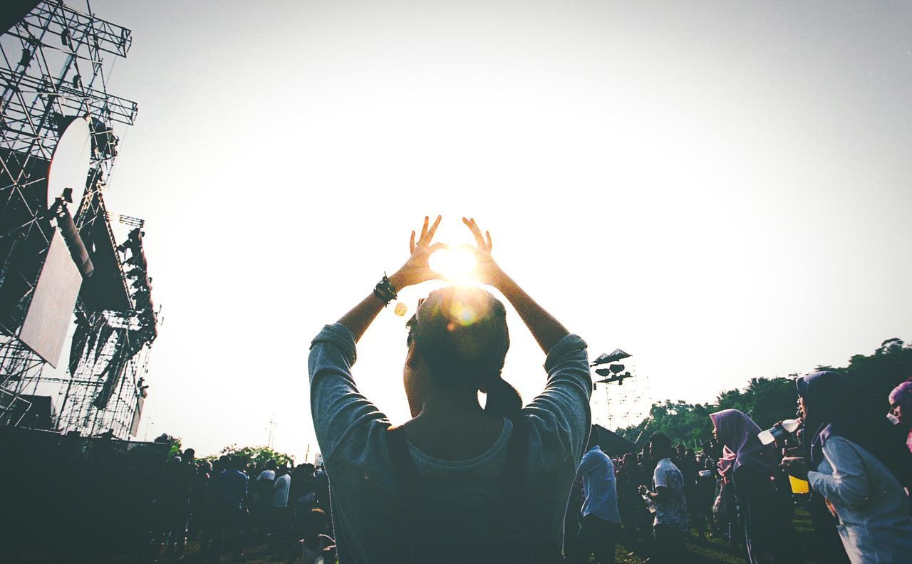 Young woman making heart shape against sun