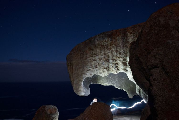 Rock formation by sea against sky at night