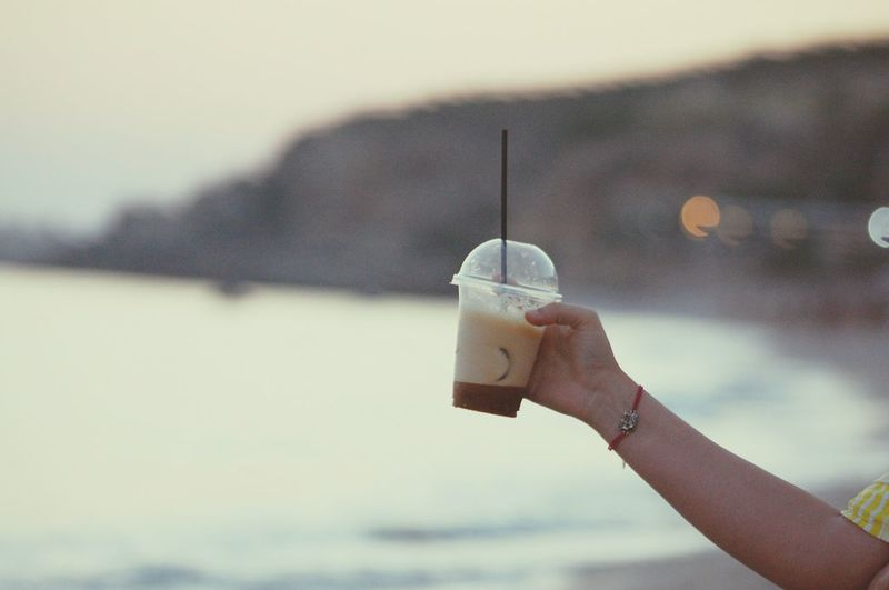 Cropped Hand Of Person Holding Coffee In Disposable Cup At Beach
