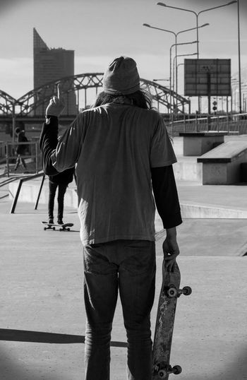 Rear View Of Men Standing In Skate Park