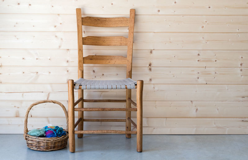Basket by wooden chair against wall