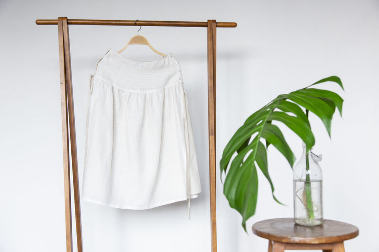 Cotton skirt on wooden hanger. Indoors  No People White Color Hanging Leaf Plant Green Color Wall - Building Feature Still Life Plant Part Close-up Nature Home Interior Wood - Material Coathanger Absence Simplicity White Background Rack Clothing Fashion Skirt