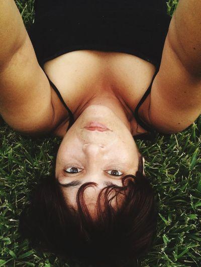 Portrait of woman lying down on grassy field