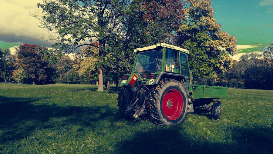 Tractor on field against trees
