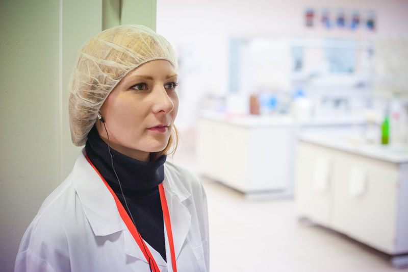 Female Doctor Wearing Surgical Cap While Working In Hospital