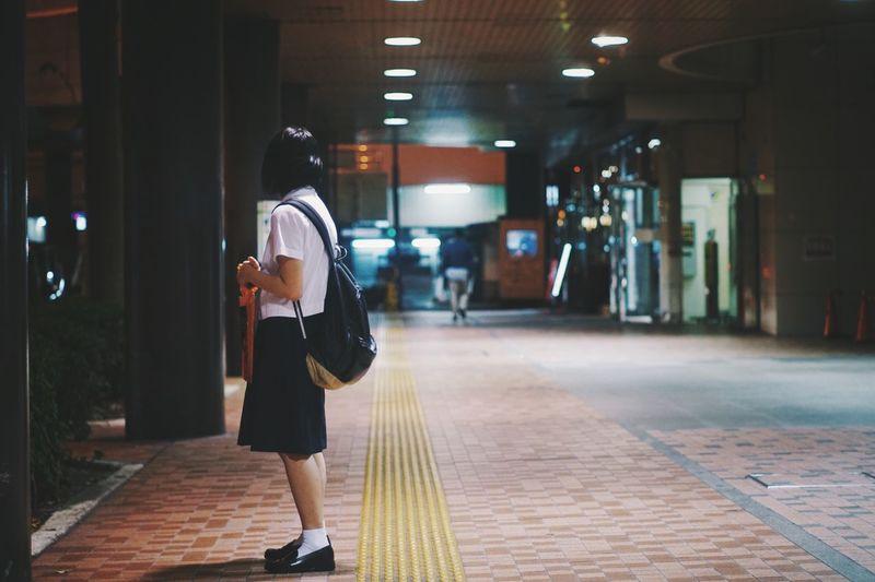 Schoolgirl standing on footpath
