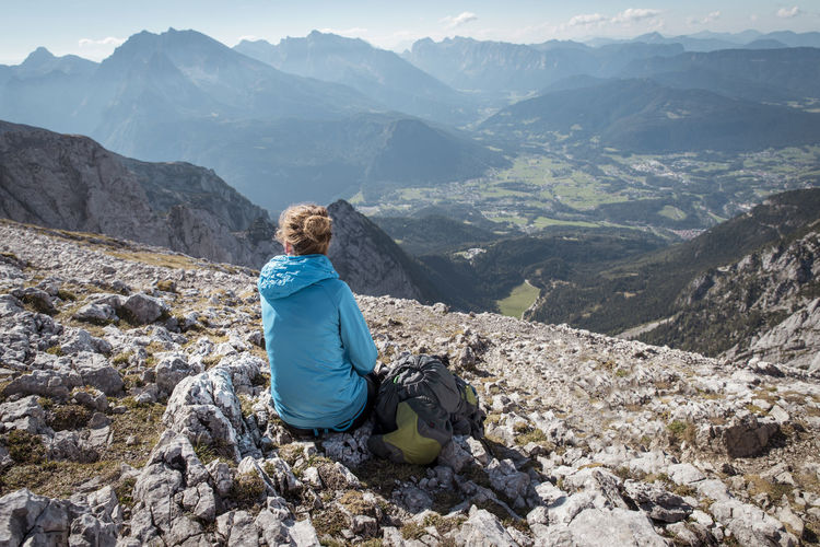 Rear view of woman sitting on top of mountain at watzmann