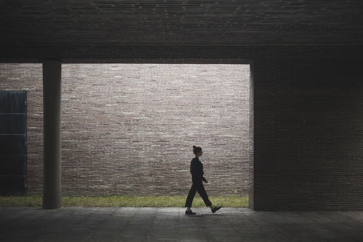 Side view of silhouette man walking against building