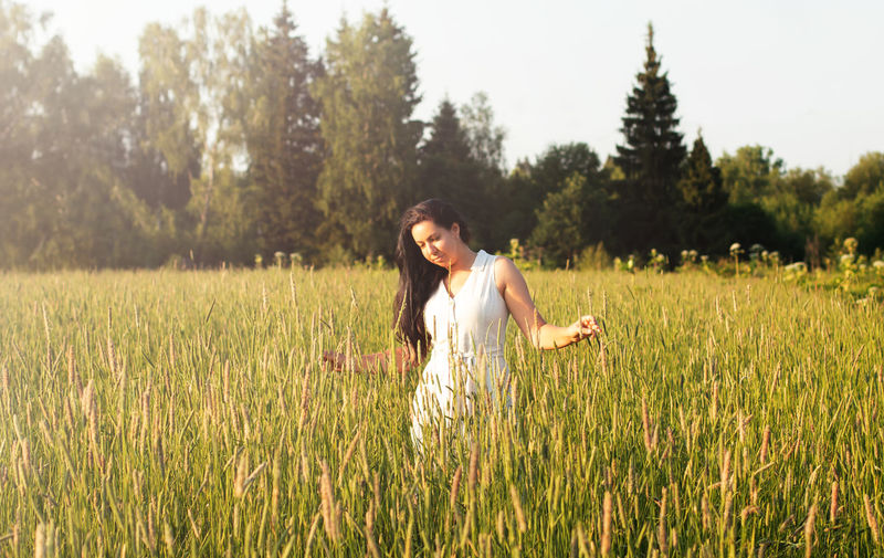 A young woman with long dark hair stands in a field with and looks at the ears of wheat.