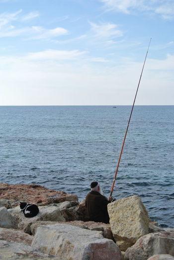 Rear view of man sitting on rock fishing in sea