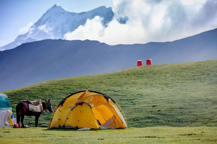"""Stay"" As the trekkers pitch their tent after a hard climb at the Bedni Bugyal which is Asia's Largest Bugyal (Meadow). The Traveler - 2018 EyeEm Awards The Great Outdoors - 2018 EyeEm Awards Mountain Cloud - Sky Sky Camping Scenics - Nature Beauty In Nature Tent Land Tranquility Day Landscape Mountain Range Non-urban Scene Environment Nature Tranquil Scene Adventure Idyllic Grass Real People"