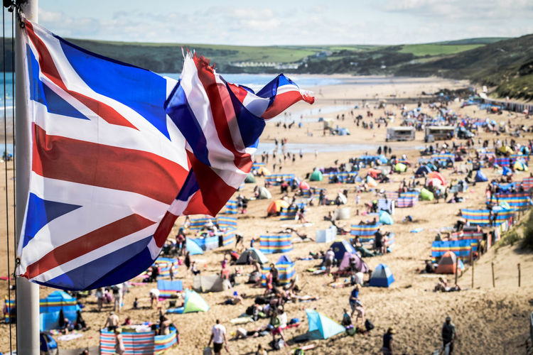 Beach British Crowd Day Flag Flag Pole Group Of Objects Landscape Large Group Of People Leisure Activity Lifestyles National Flag Outdoors Person Seascape Seaside Selective Focus Union Flag British Holiday Holiday Live For The Story