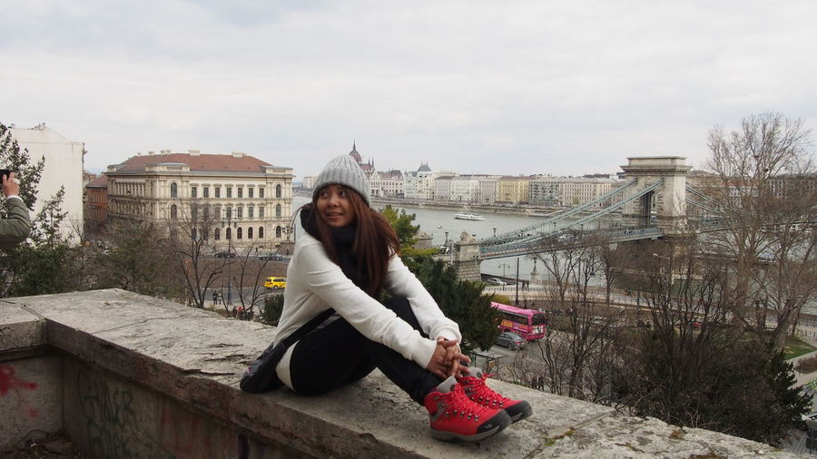 Full length of woman sitting on retaining wall with szechenyi chain bridge in background