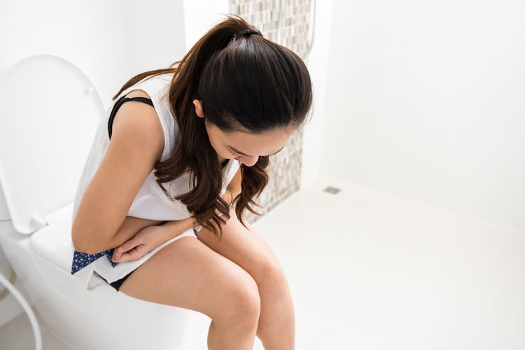 High angle view of woman with hands on stomach sitting in toilet