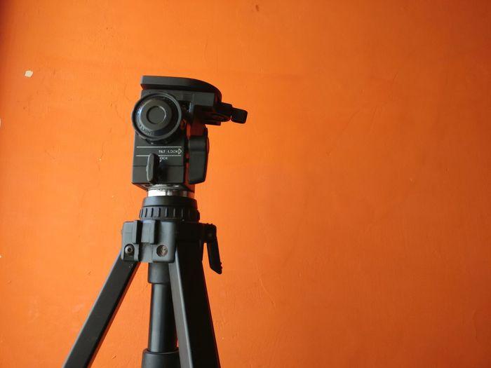 Close-Up Of Camera Against Orange Background