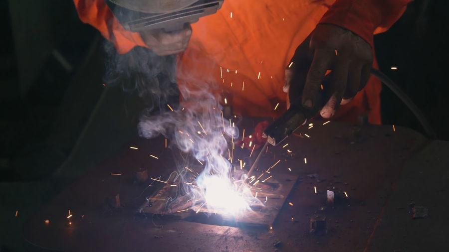 Midsection of man welding metal in workshop