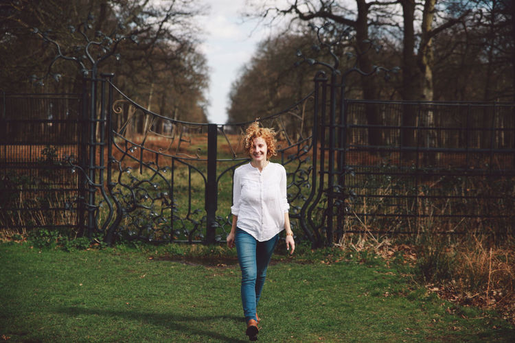 Smiling young woman on grassy field walking against closed gate