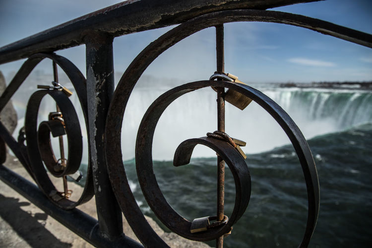 Close-up of bicycle wheel by railing against river