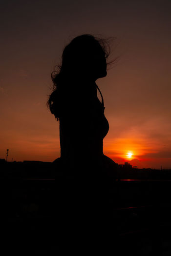 Silhouette woman looking at sunset