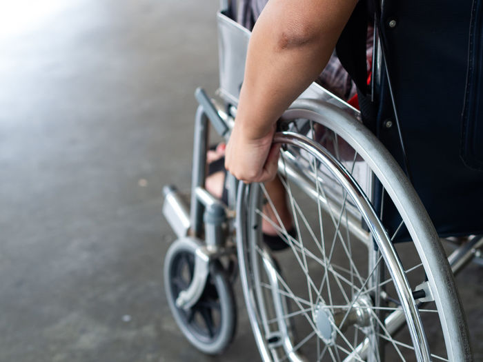Low section of person sitting on wheelchair in city