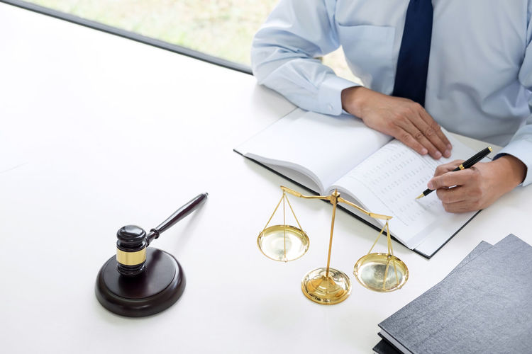 Midsection Of Lawyer Writing In Book On Desk