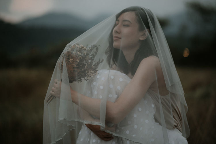 Bride Hugging Knees While Sitting Outdoors