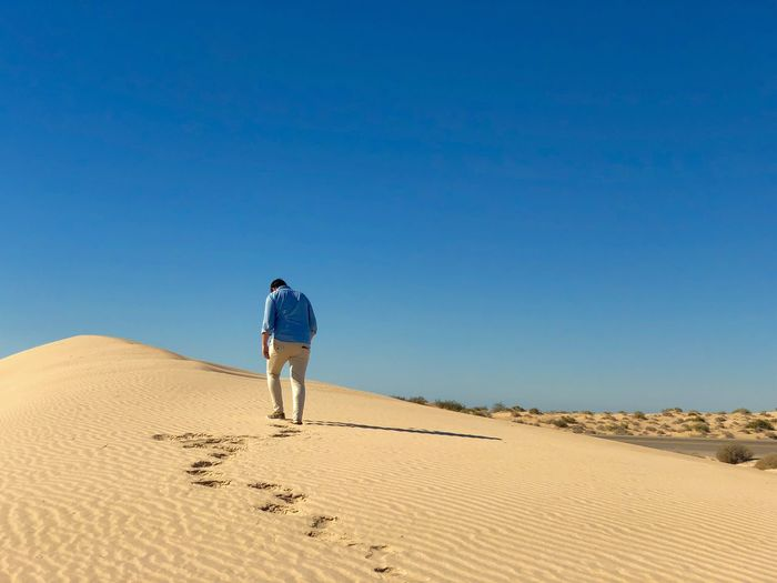 Rear view of man walking on sand in desert against sky