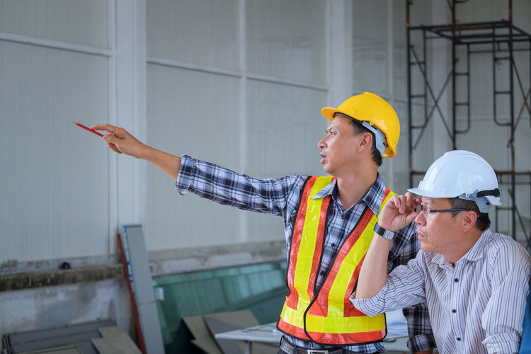 Architect Pointing While Explaining Coworker At Construction Site