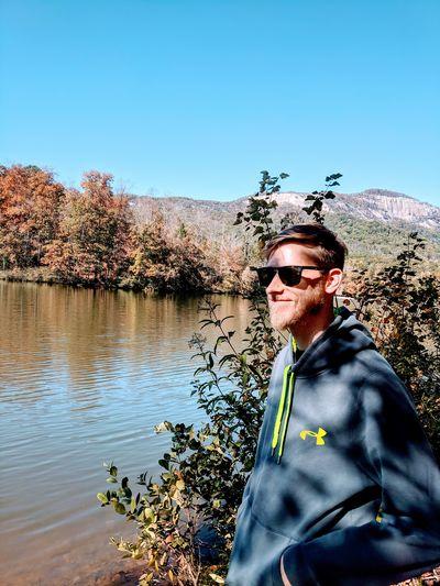 Portrait of man wearing hat by lake against sky