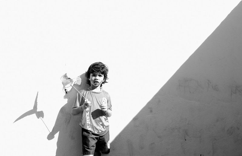 Boy Holding Paper Pigeon Toy While Standing Against Wall