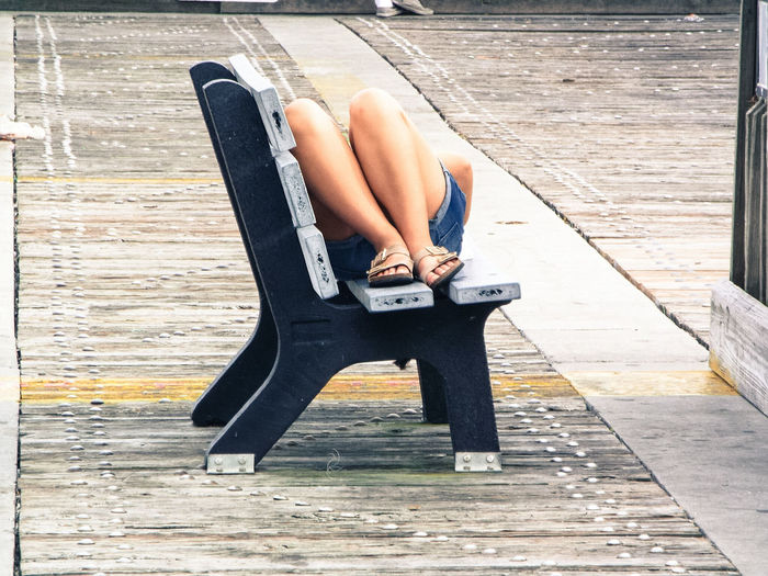 Low section of woman lying on bench at park