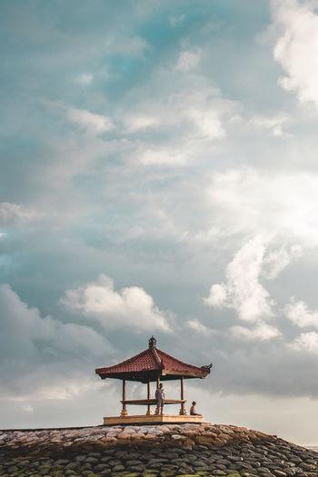 Low angel view of people by gazebo against sky