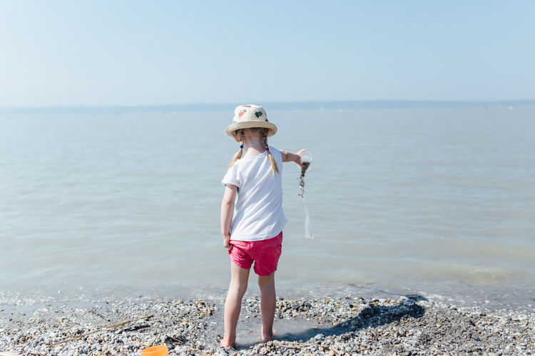 Girl wearing hat pouring water from container on shore at beach during sunny day