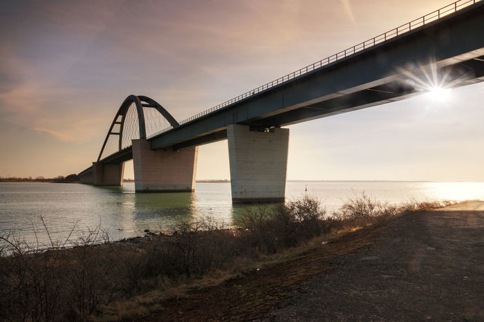 Fehmarn Sound Bridge in sunset (German: Fehmarnsundbrücke), suspension bridge with steel arches connecting the German mainland with the island in the Baltic Sea and belongs to the Vogelfluglinie Baltic Sea Fehmarnsundbrücke Vogelfluglinie Arch Architecture Belt  Bridge Built Structure Cloud - Sky Coast Connection Fehmarn Nature No People Outdoors Sea Sky Steel Sun Sunset Suspension Bridge Transportation Water