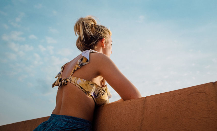Midsection of woman sitting against sky
